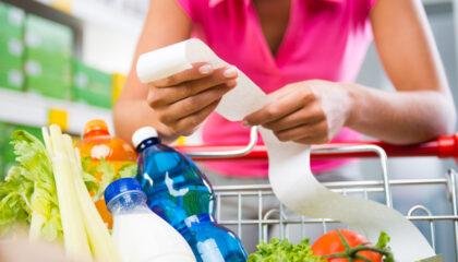 Frau mit Einkaufswagen prüft Kassenzettel